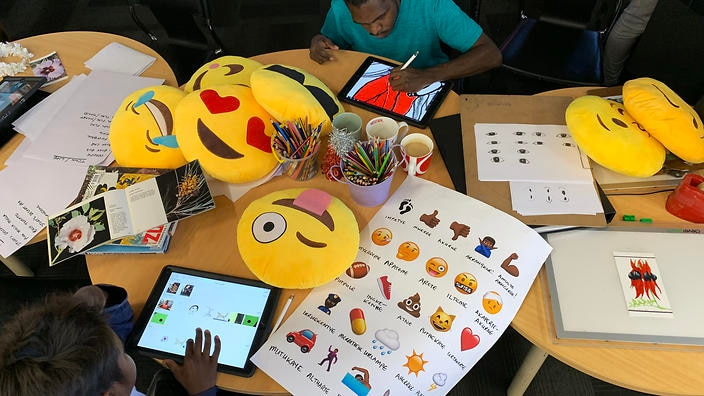 Supporting artist Graham Wilfred Jnr mentors a young participant to make his own emoji.