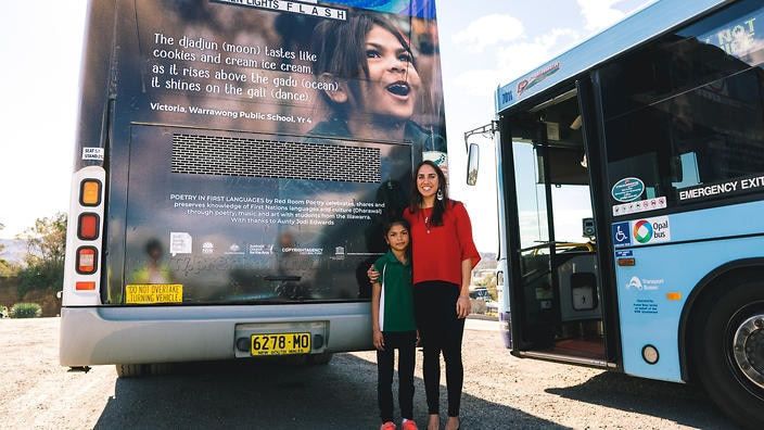 Kirli Saunders and young poet Victoria with her poem on the back of a bus