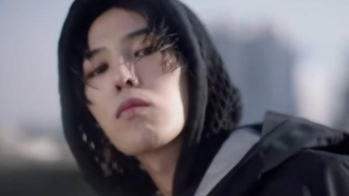 G-Dragon is kissing the air on the side of a massive