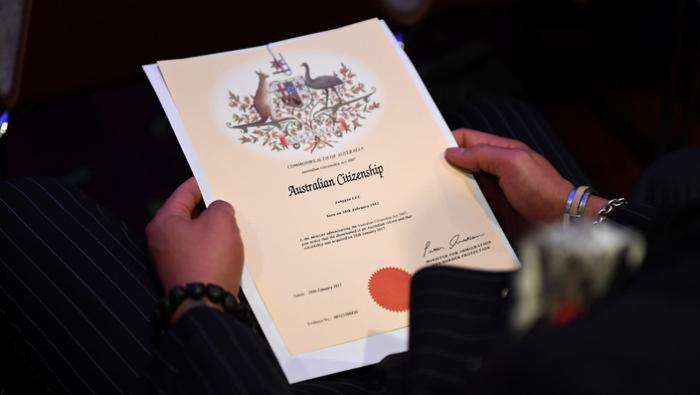 An Australian citizenship recipient holds his certificate during a citizenship ceremony on Australia Day.