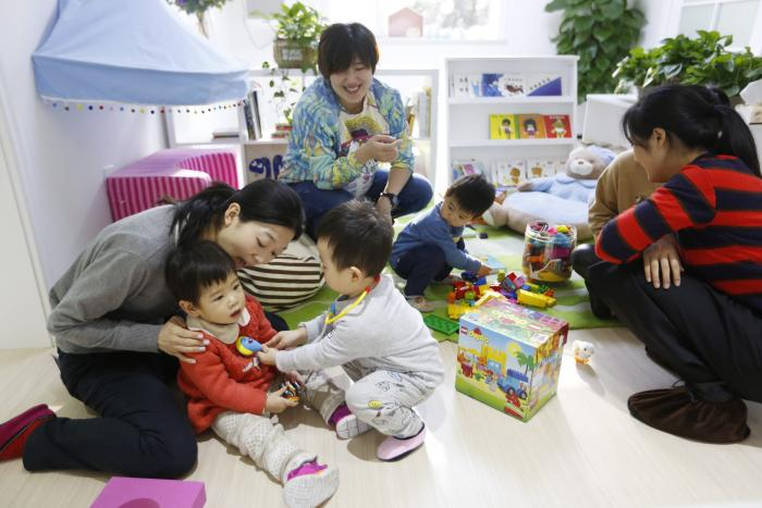 Chinese parents and their children playing together at the Magic International Daycare, a high end child care center in Beijing, China
