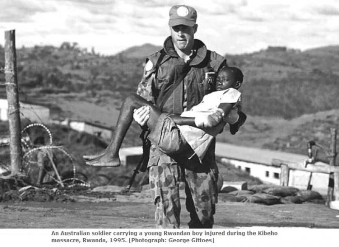Australian soldier carrying a young Rwandan boy injured in Kibeho.