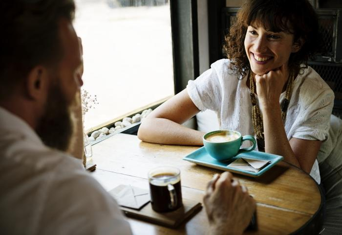 Woman smiling to a man while they're having coffee