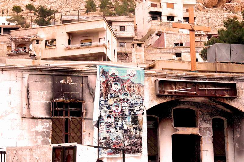 A burnt-out Syrian church displays a memorial banner to civilians killed in an attack.