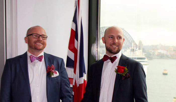 Two grooms hold hands in front of a union jack, the Harbor Bridge is visible in the background.