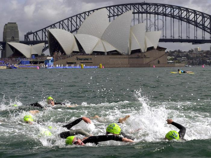 Athletes swim past the Sydney Opera House during the first leg of the women's triathlon at the 2000 Summer Olympic Games in Sydney, Saturday, Sept. 16, 2000. (AP Photo/Robert F. Bukaty)