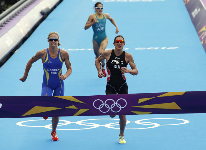 Gold-medallist Switzerland's Nicola Spirig, right, silver-medallist Sweden's Lisa Norden, left, and bronze-medallist Australia's Erin Densham compete in the triathlon at the 2012 Summer Olympics, Saturday, Aug. 4, 2012, in London. (AP Photo/Jae C. Hong)