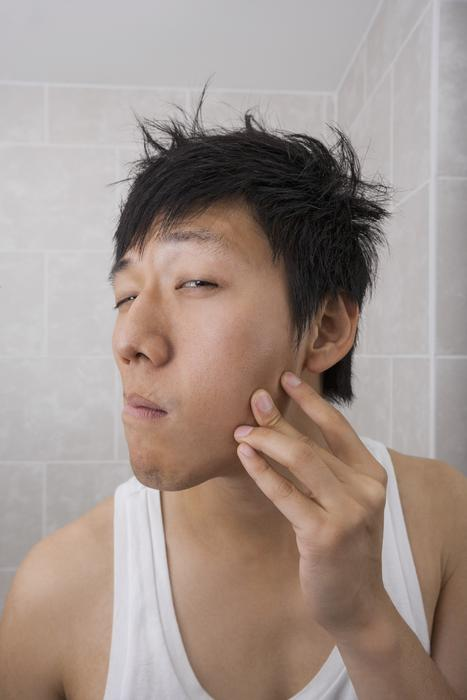 Man examining his face in bathroom