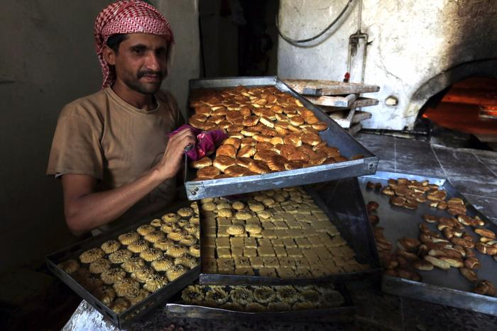 A Yemeni baker prepares cakes at a bakery ahead of Eid al Adha celebrations in the old city of Sana'a, Yemen.