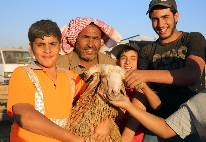 A Jordanian family take a picture with a sheep after buying it in Amman, Jordan.