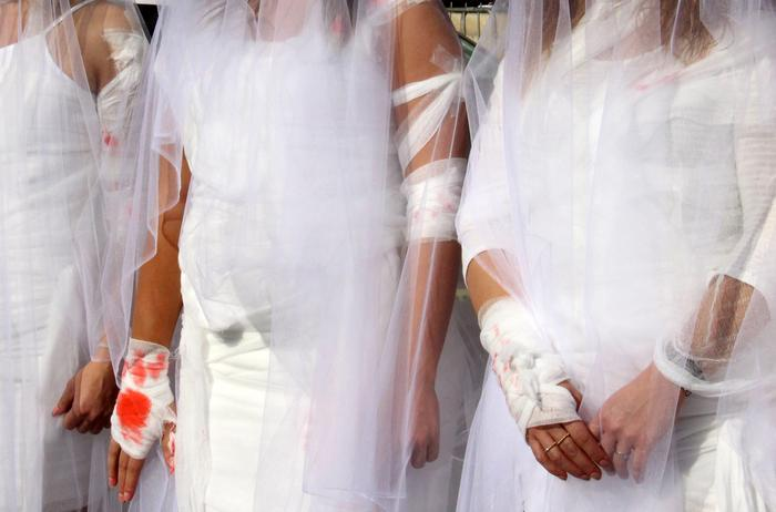 Activists from the Lebanese NGO Abaad dress as brides and wearing injury patches during a protest against article 522 in the Lebanese penal code.