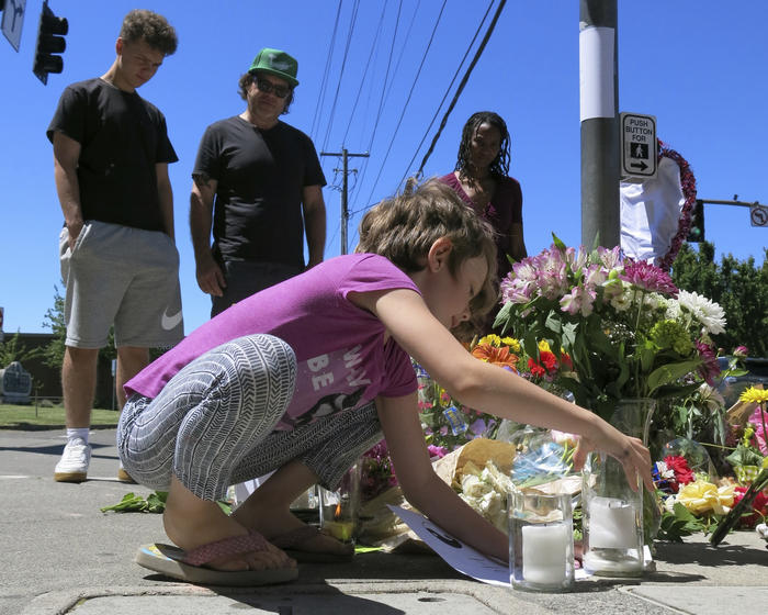 Coco Douglas, 8, leaves a handmade sign and rocks she painted at a memorial in Portland for two bystanders stabbed to death following an anti-Muslim attack.