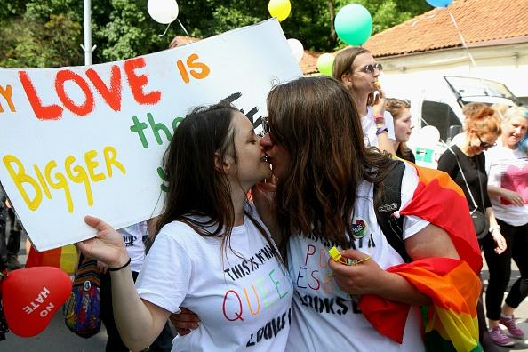 """Girls kiss as they take part in the gay rights """"Baltic Pride 2016"""" march on June 17, 2016, in Vilnius, Lithuania. / AFP / Petras Malukas        (Photo credit should read PETRAS MALUKAS/AFP/Getty Images)"""