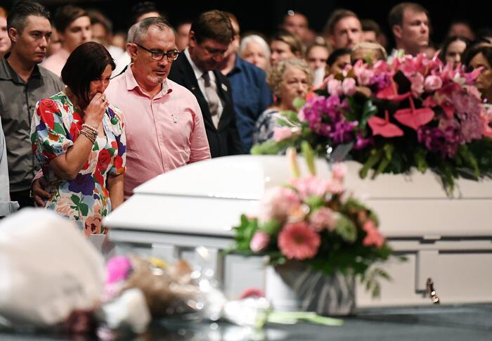 Hannah Clarke and her three children's remains are being laid to rest in a single white coffin, adorned with pink flowers.