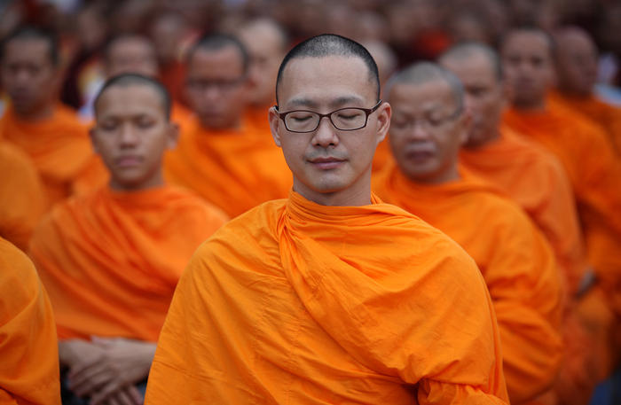 Thai Buddhist monks meditate during a ceremony to receive alms from Myanmar and Thai devotees close to Golden Palace in Mandalay, the second largest city in Myanmar, Sunday Sept. 20, 2015. (AP Photo/Hkun Lat)