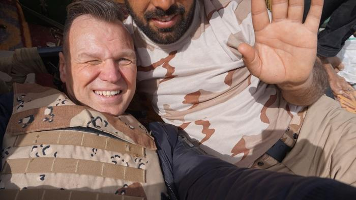 Andrew Drury takes a selfie in a trench in Iraq