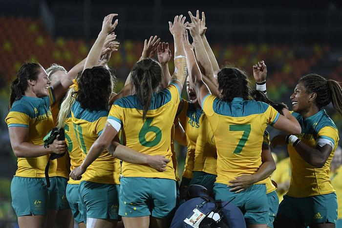 Australia's players celebrate victory in the womens rugby sevens gold medal match between New Zealand and Australia.