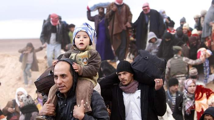 New arrivals of Syrian refugees cross the Jordan border with Syria.