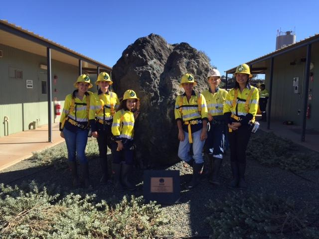 students wearing reflective gear posing at a giant rock
