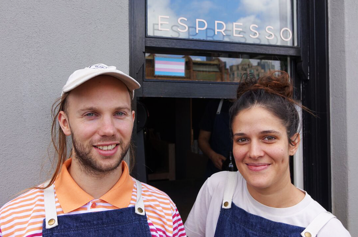 Chrissie and Zach stand in front of the transgender flag in the window of Assembly cafe.