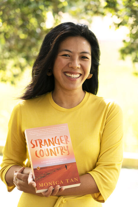 Monica Tan holding her book, Stranger Country.