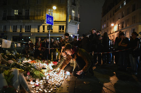 People place flowers and candles on the pavement near the scene of the attack on the Bataclan Theatre.