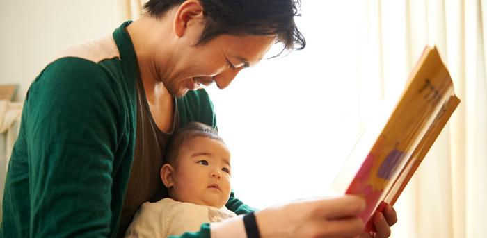 a father reads to his baby child