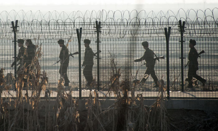 North Korean soldiers patrol next to the border fence near the town of Sinuiju across from the Chinese border town of Dandong (image: 2016).