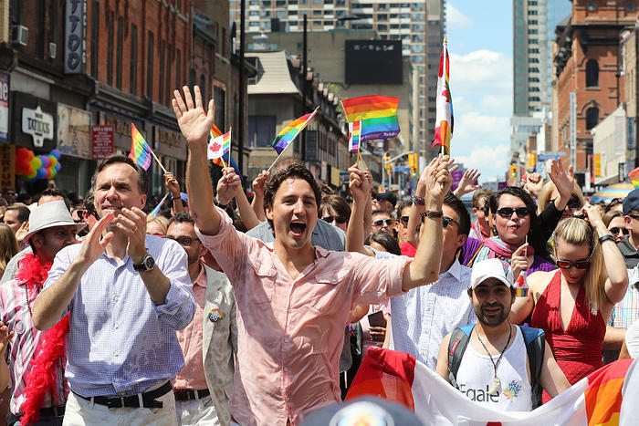 Syrian refugee Bassel Mcleash walks next to Canadian Prime Minister Justin Trudeau in Toronto's Pride Parade.