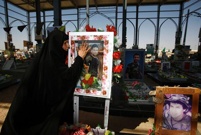An Iraqi woman next to graves of relatives as she visits the Wadi al-Salam (Valley of Peace) cemetery on Eid al Adha in the Shiite holy city of Najaf in central Iraq