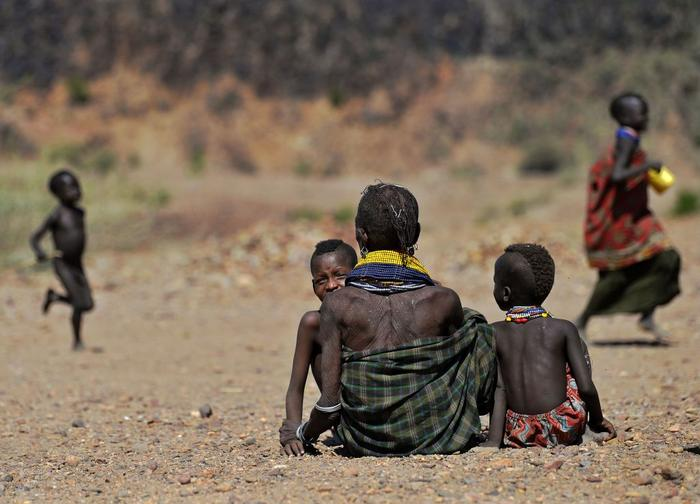 A woman waits with her children to get food rations near Lokitaung in northern Kenya's Turkana county where a biting drought has ravaged livestock population.