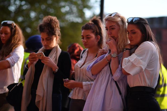 People pause in front of floral tributes in Albert Square in Manchester, in solidarity with those killed and injured in attack at the Ariana Grande concert.