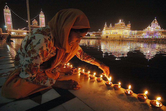Indian devotees light candles in front o