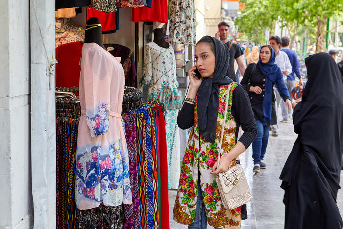 Girl uses smartphone near shop with bright clothes, Isfahan, Iran.