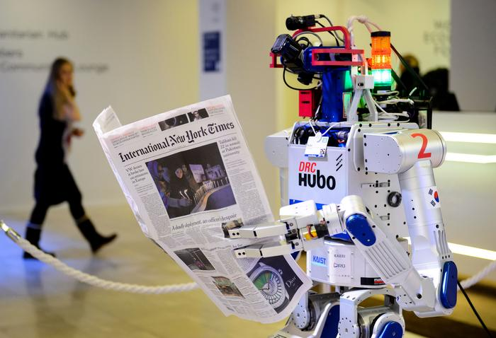 Hubo robot holding a newspaper