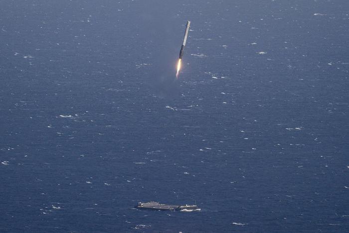 space x rocket approaching a landing platform in the ocean