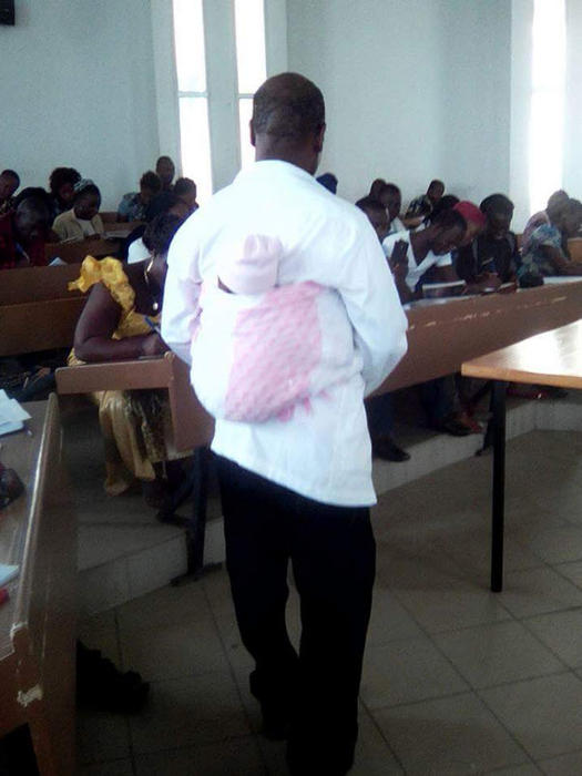 Honore Kahi carries a student's baby in class.