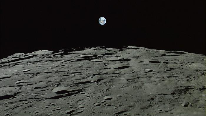 the earth rising above the moon surface