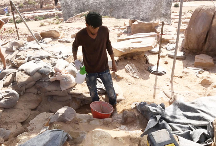 An archaeologist makes mortar to shore up the outer walls of the Temple of Winged Lions. (Dieter Knierim)