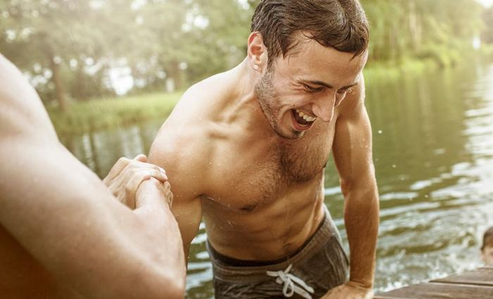 a shirtless muscled man accepts another mans help to pull himelf out of water he's been swimming in