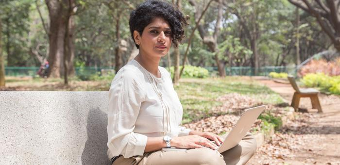 Preethi Herman sits on a bench with a laptop.