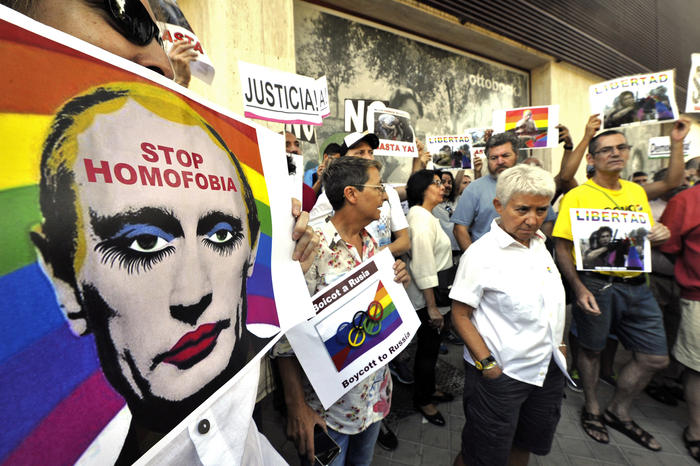 Demonstrators hold up anti-Putin placards at rally at Russian embassy in Spain, 2013.