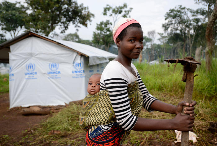 Burundi refugee mother carries her baby while she farms the plot of land that belongs to their shelter in the UNHCR refugee camp Nduta in the Kigoma district Tanzania.