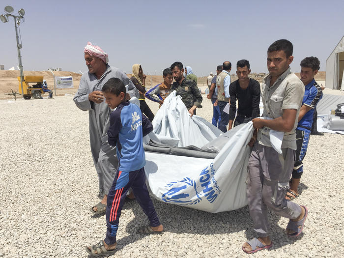 Families fleeing militant extremist groups and heavy bombing in western Mosul collect their tents and emergency kits upon arrival at Hasansham U2 camp.