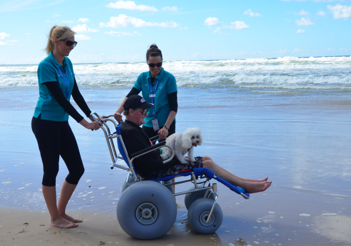 Tony Lambert was the first Gold Coast Health palliative care patient to use a beach wheelchair when occupational therapists Olivia Palac and Julie-Ann Hendry.