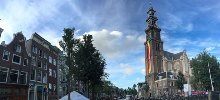 An old and prominent church flies a longthy rainbow banner down its front-most tower facing onto a canal