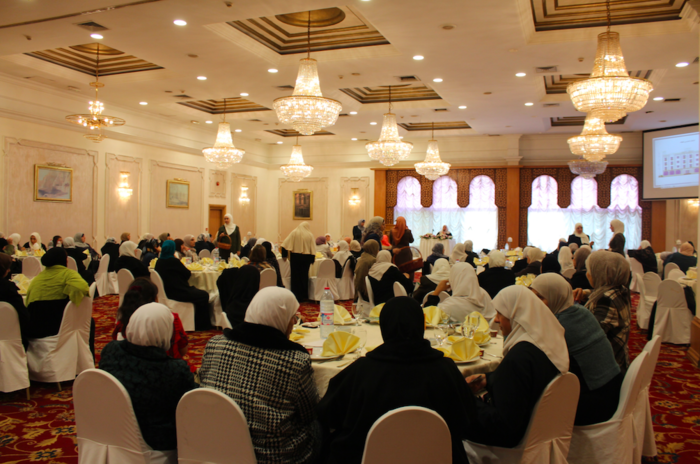 A crowded room of Islamic women listen intently to the Sheikha talk about the importance of good deeds.