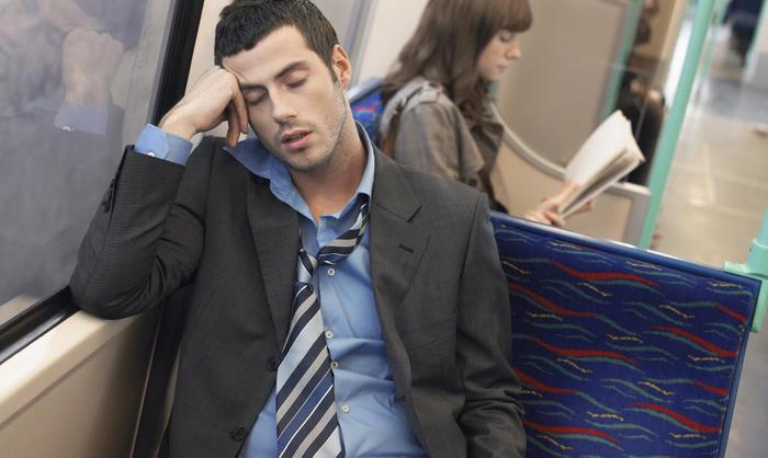 man asleep on a train