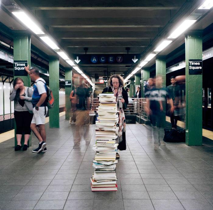 A woman looks at a tower of books in Times Square subway station.