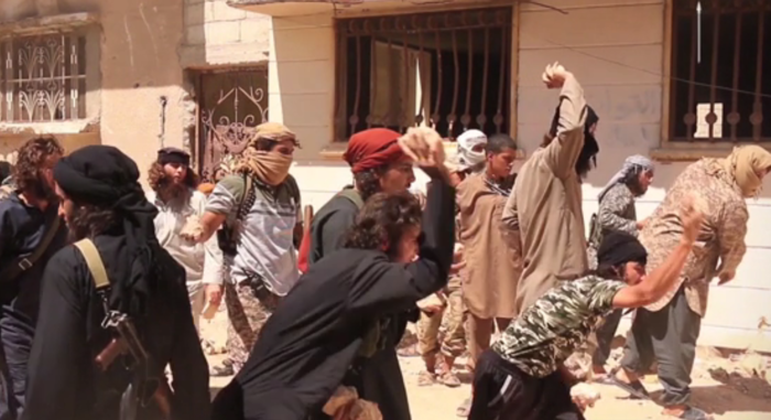 Men throw stones at the body of a murdered man in an ISIS propaganda video.
